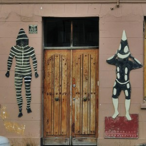 Entrance to Remezon Restaurant decorated with artwork depicting Yamana People with bark masks & body painting